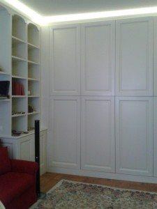 armadio in listellare di legno laccato bianco con libreria ad angolo